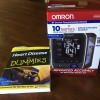 "A photo of a blood pressure monitor and the book ""Heart Disease for Dummies"""